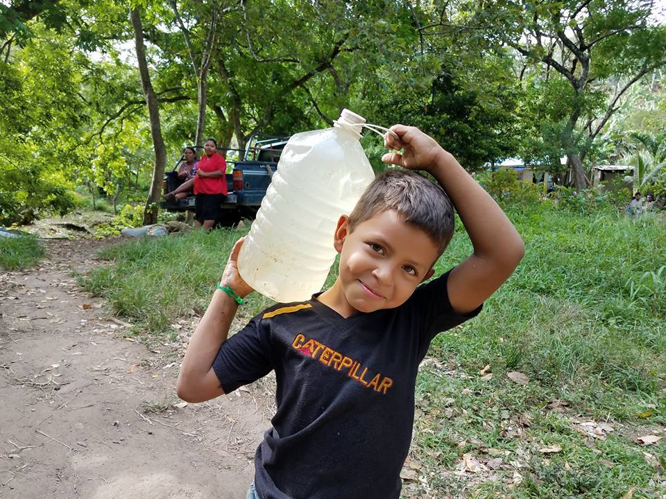 Smiling boy carrying a jug of dirty water in Colonia Alden Webster